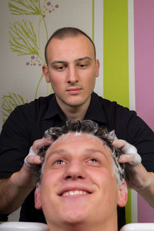young style: Portrait of handsome male client getting his hair washed at salon