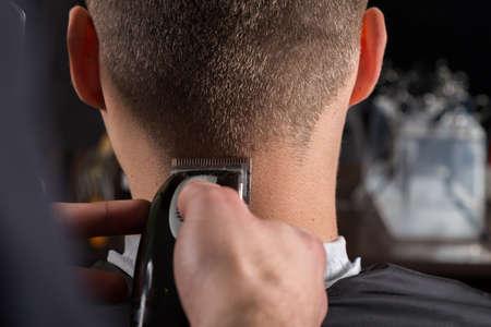 hombres jovenes: corte de pelo de los clientes con una cortadora de cabello el�ctrica en el sal�n de belleza peluquer�a Foto de archivo