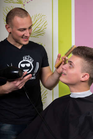 hairstyling: Mens hairstyling and haircutting with hair clipper and scissor in a barber shop or hair salon. Stock Photo