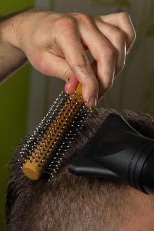 peluquería: peluquero hace el pelo negro con el cepillo y secador de pelo del cliente en el salón de peluquería profesional