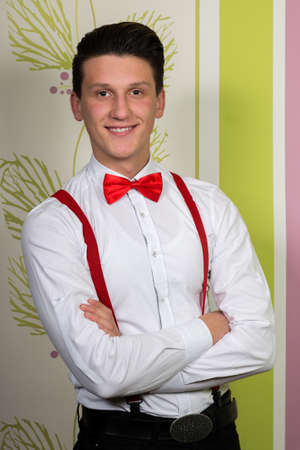 A young smiling man with a red bow and suspenders posing on colorful background.