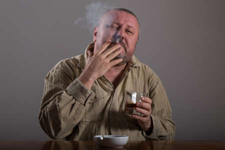 forlorn: Alcoholism: portrait of a lonely, desperate man drinking alcohol and smoking cigarette