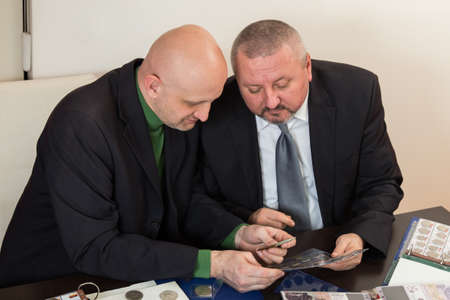 cyrillic: Two numismatists examines  collection of coin Stock Photo