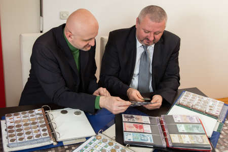 numismatist: Two numismatists examines  collection of coin Stock Photo
