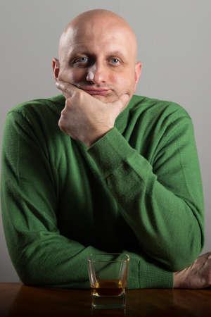 wasted: Bald headed man drinking whiskey Stock Photo