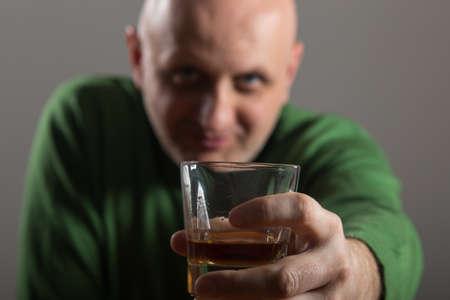 headed: Bald headed man drinking whiskey Stock Photo