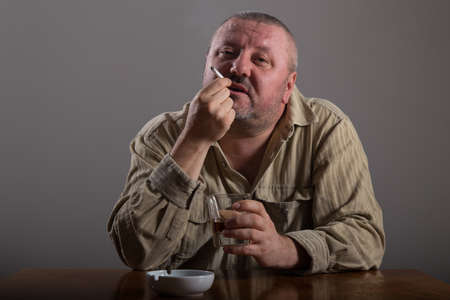 crossed cigarette: Alcoholism: portrait of a lonely, desperate man drinking alcohol and smoking cigarette