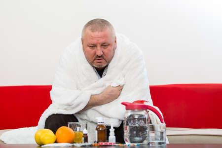 in pajama: Sick  man wearing pajama suffering cold and winter flu virus having medicine Stock Photo