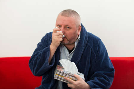 man face: Man having a cold holding tissue with box full of tissues