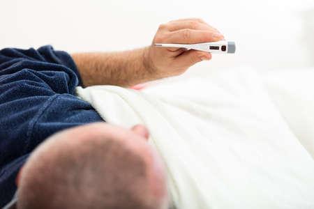 Immagine drammatica di un uomo malato che a letto con la febbre