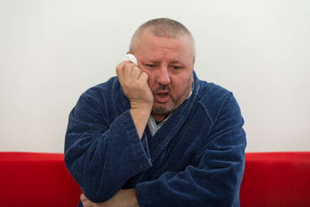 tired face: Close-up of a man with tissue in his nose. Stock Photo
