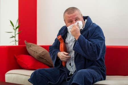 wärmflasche: Kranker Mann im Bett mit Kopfschmerzen eine Wärmflasche hält