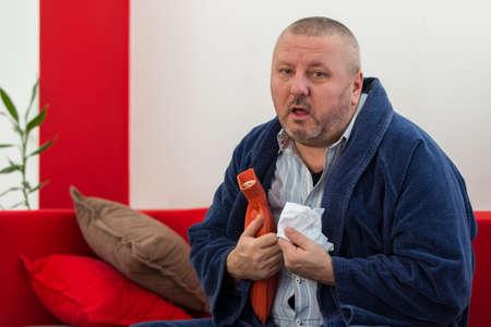 Hombre enfermo en la cama que tiene un dolor de cabeza que sostiene una botella de agua caliente Foto de archivo