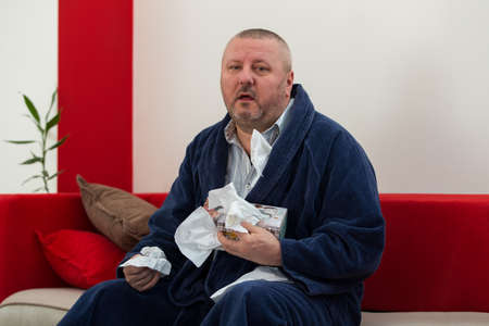 men face: Man having a cold holding tissue with box full of tissues
