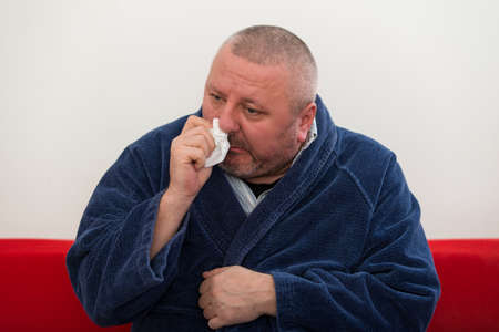 men face: Close-up of a man with tissue in his nose. Stock Photo