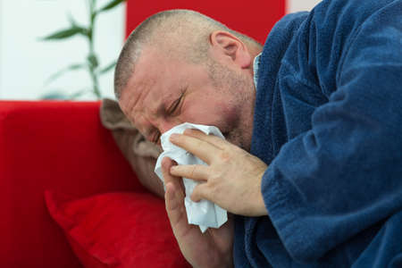 18 19: Man blowing his nose in his living room Stock Photo