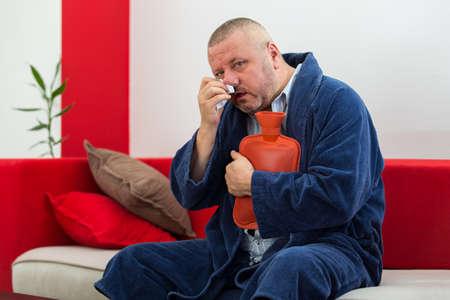 w�rmflasche: Sick man in bed having a headache holding a hot-water bottle
