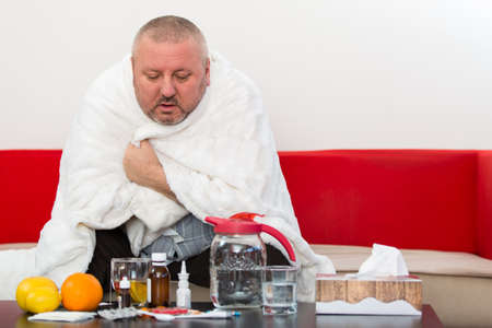 Sick  man wearing pajama suffering cold and winter flu virus having medicine Banco de Imagens