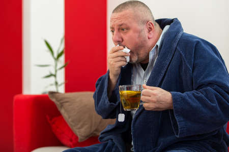 Ill man blowing his nose with paper napkin and drinking tea at home