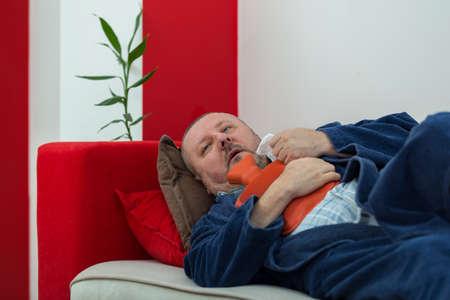 Sick man in bed having a headache holding a hot-water bottle