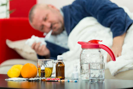Sick man in bed with drugs and fruit on table