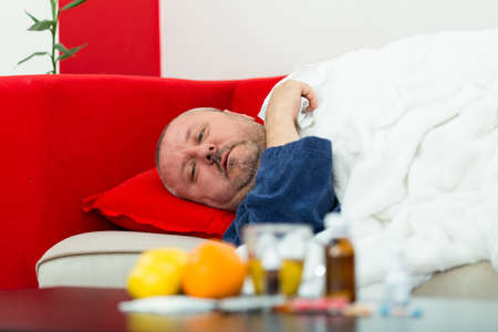 c vitamin: Sick man in bed with drugs and fruit on table