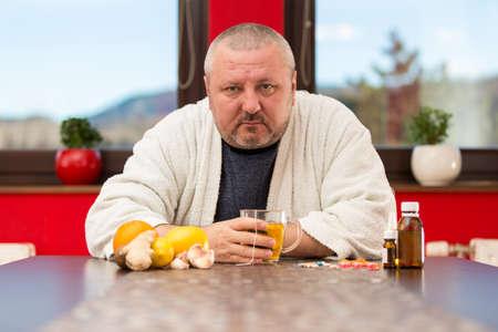 Sick man suffering cold and winter flu virus drinking tea