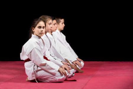 Children in kimono sitting on tatami on martial arts seminar. Selective focus.