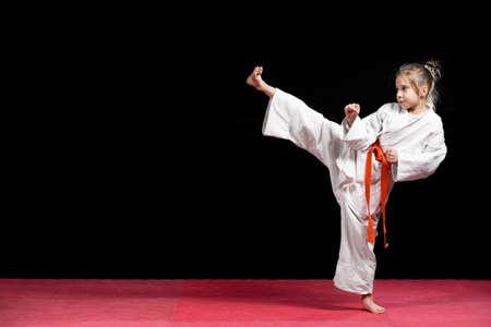 Little girl practice karate isolated on black.