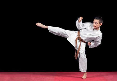 Karate boy in white kimono fighting isolated on black  background.
