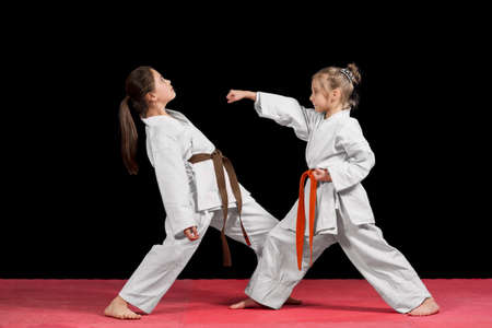 Two girls in kimono are training paired exercises karate.