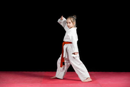 Little girl practice karate isolated on black. Banco de Imagens - 57740622