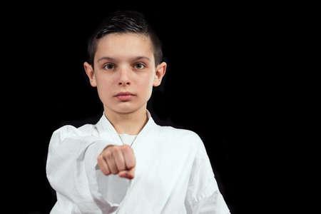 karate boy: Karate boy in white kimono fighting isolated on black  background.