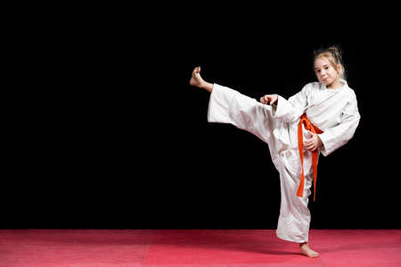 Little girl practice karate isolated on black.