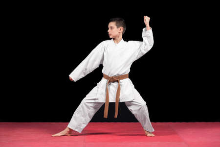 Karate boy in white kimono fighting isolated on black  background.