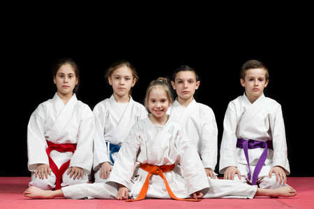 sensei: Children in kimono sitting on tatami on martial arts seminar. Selective focus.