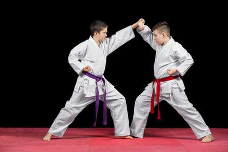 Two boys in white kimono fighting isolated on black background.