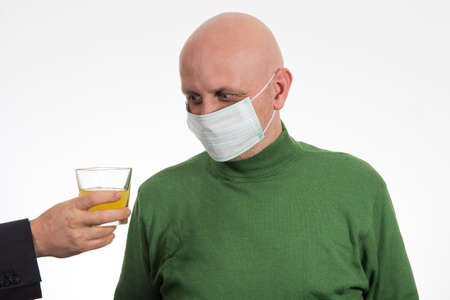 Flu illness young man in medicine healthcare mask looking at juice