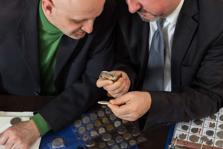 Two numismatists examines  collection of coin Banco de Imagens
