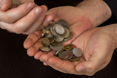numismatist: Close up of mans hands and pile of old coins
