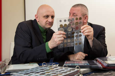 Two numismatists examines  collection of coin Archivio Fotografico
