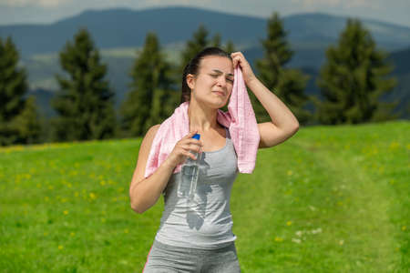 Portrait of woman drinking water outdoor.
