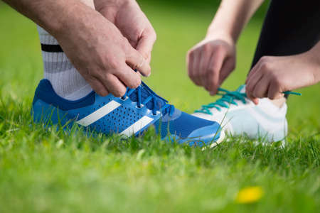 Running shoes - closeup of tying shoe laces. Sport fitness runners getting ready for jogging outdoors on forest path in spring or summer.