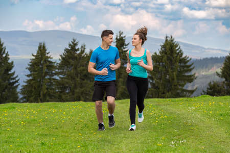 Young couple running in nature on sunny day