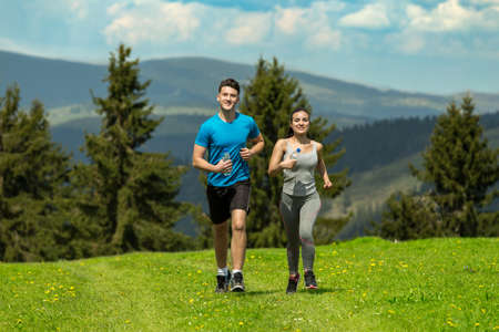Portrait of cheerful Caucasian couple running outdoors.