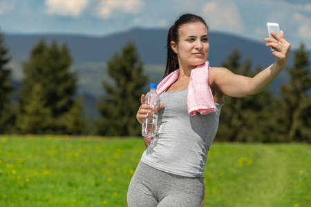 Pretty atlethic woman taking selfie in nature.