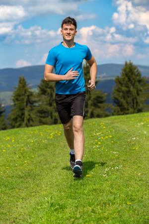 Running fitness man sprinting outdoors in beautiful landscape. Fit male runner training for marathon. Caucasian sport model. Banco de Imagens
