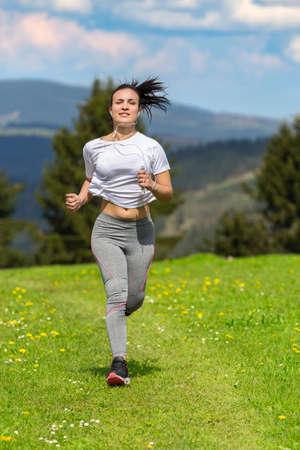 Pretty sporty woman jogging at park. Banco de Imagens
