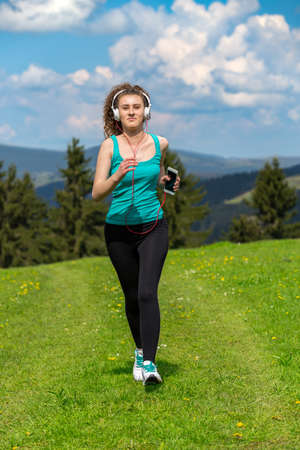 Jogging woman running in sunshine on beautiful summer day and listening a music in headphones. Sport fitness model caucasian ethnicity training outdoor for marathon. Banco de Imagens