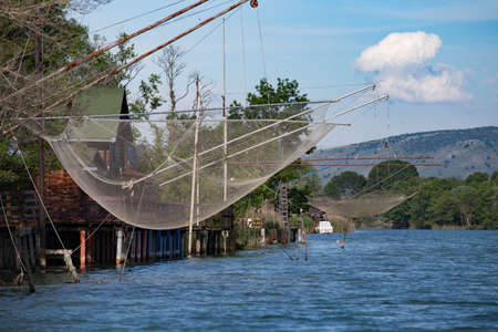 Fisherman house and net on the river in Montenegro.